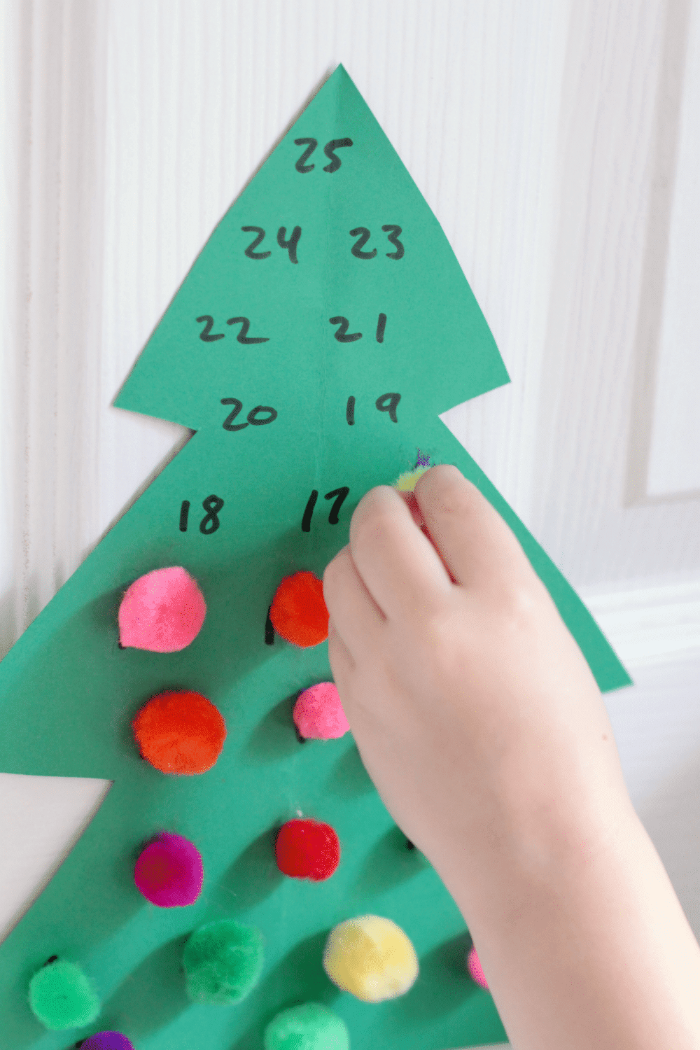 Looking for an advent calendar for kids? This pom pom Christmas tree advent calendar is super easy and makes a great Christmas craft for kids!