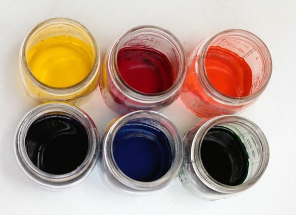 How to make rainbow slime: Yellow, red, orange, green, blue, and purple dye in mason jars.