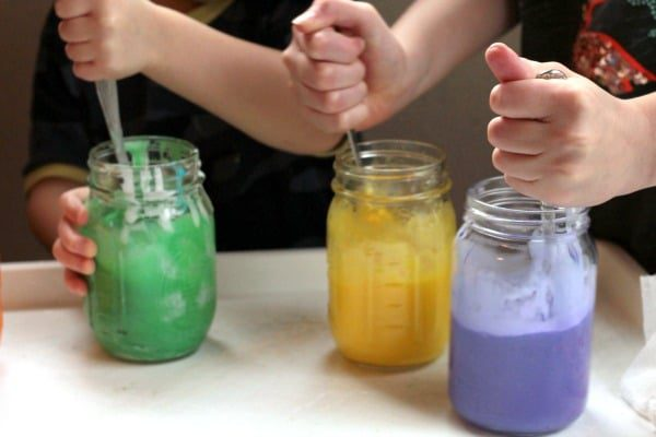 Kid hands stirring jelly rainbow slime.