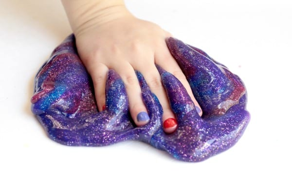 Hand sinking into blue, pink, and purple galaxy slime recipe.