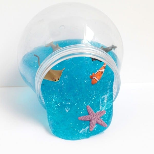 Sparkling blue ocean slime recipe in a fishbowl with ocean toys on top.
