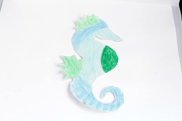 Colored seahorse craft made from a paper plate.
