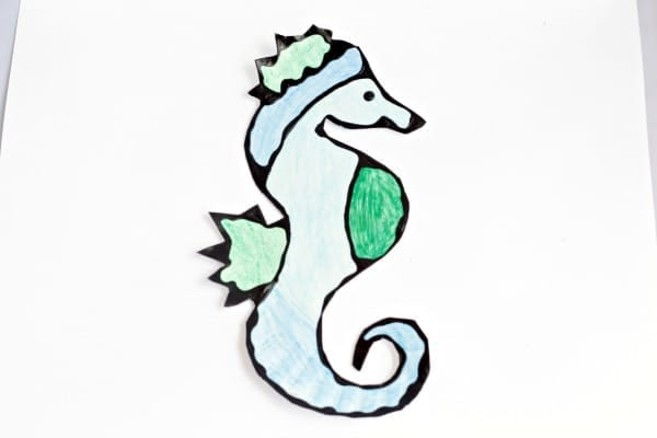 Black glue outline of the paper plate seahorse, colored blue, dark green, and light green.