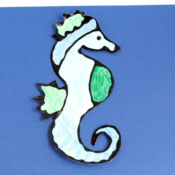 Completed seahorse craft for preschool on a blue background.