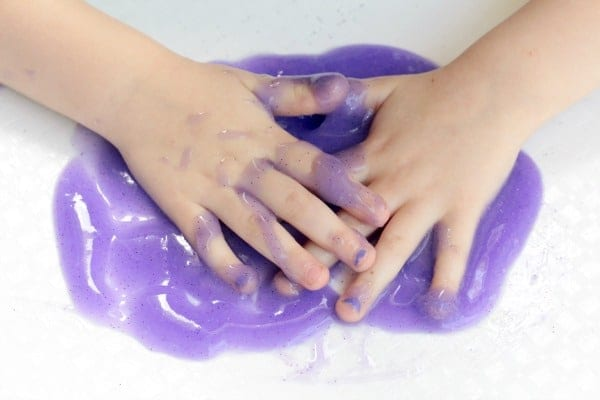 Child playing with purple slime with baking soda.