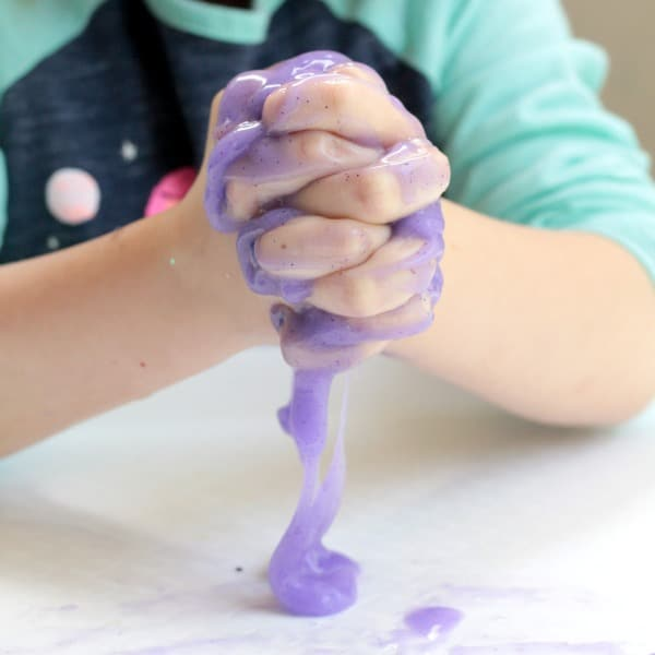 Child hands squeezing slime with baking soda and glue.
