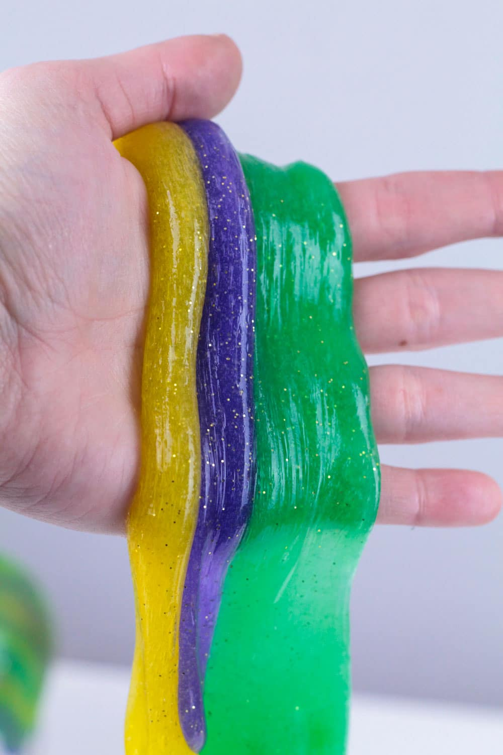 Holiday slime recipes are so much fun! This Mardi Gras slime recipe is the perfect slime recipe for Mardi Gras! The simple slime recipe is so colorful and stretchy, it's the perfect Mardi Gras activity for kids!