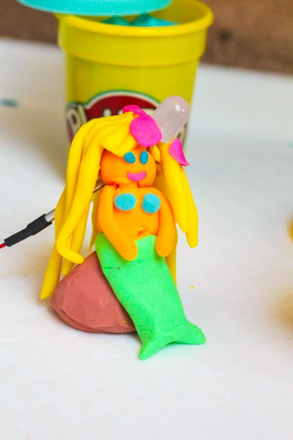 Squishy Circuits mermaid with orange skin, a green tail, yellow hair, a pink flower, and a light-up flower bow.