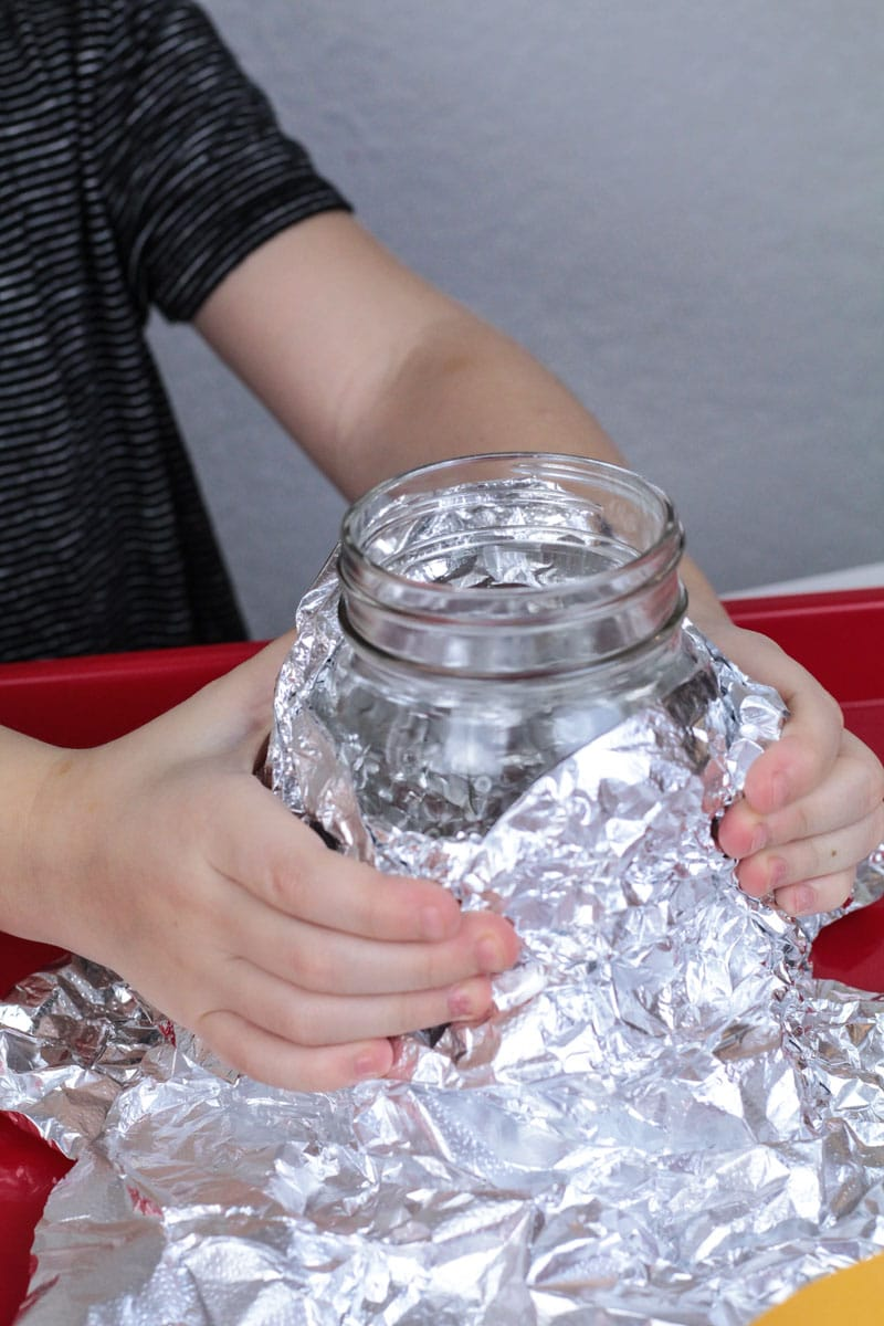 Girl wraps aluminum foil around a jar making a baking soda and vinegar volcano