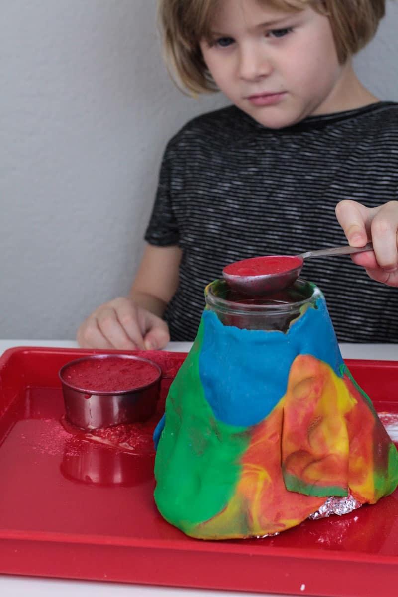 Girl pouring vinegar into baking soda and vinegar volcano