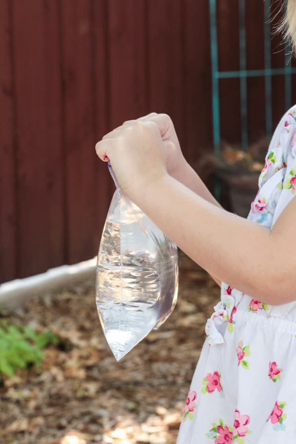 Girl holding plastic bag filled with water getting ready for the magic no leak bag experiment.