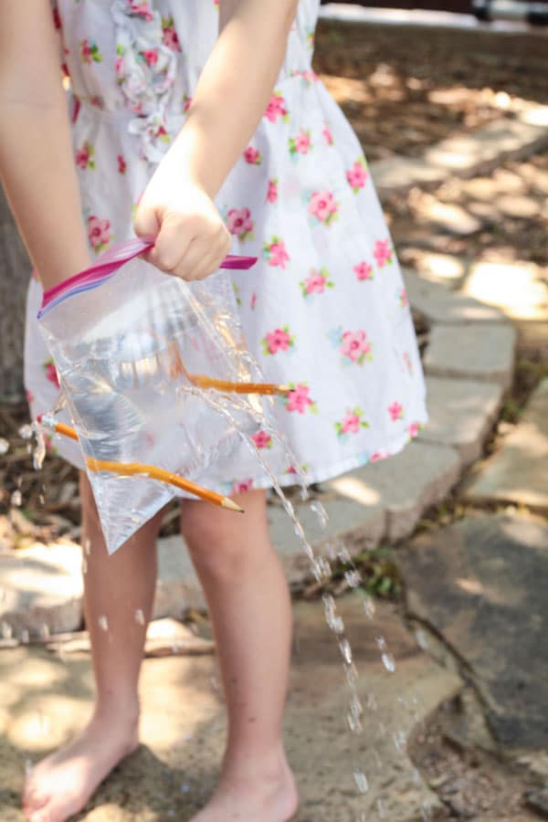 Girl removing pencils from the leak proof bag experiment