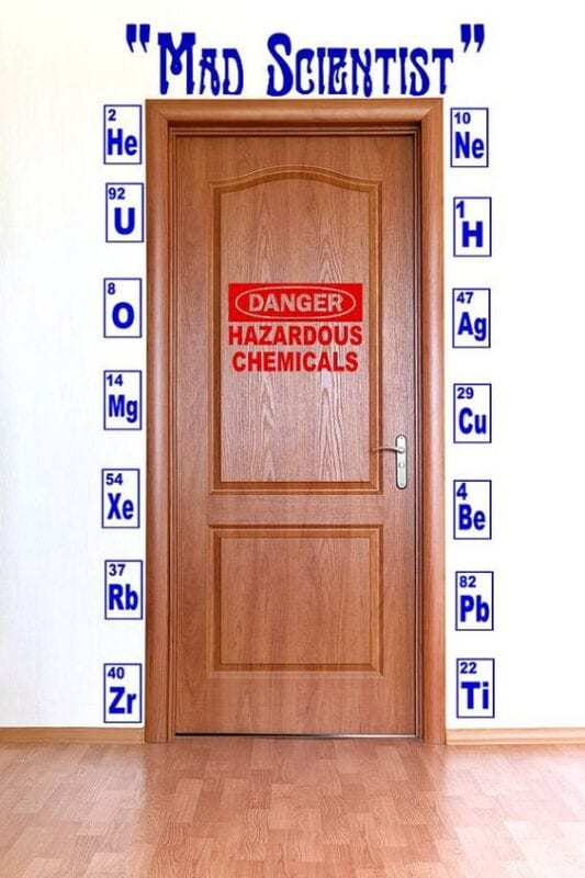 "A halloween science classroom door decorated with elements and says ""danger hazardous chemicals"""