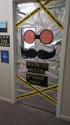 "A halloween classroom door decorated with sliver paper and caution tape with safety goggles and a mustache that says ""restricted access third grade only"""