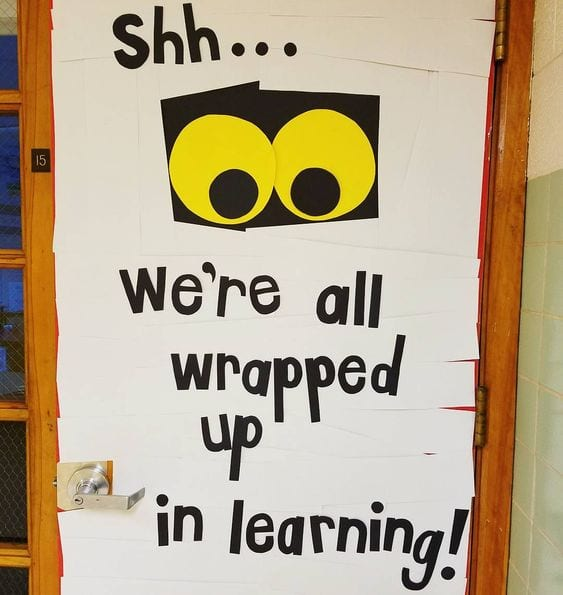 "A halloween classroom door covered in paper strips to look like a mummy with big eyes. The door says ""shh, we're wrapped up in learning."""